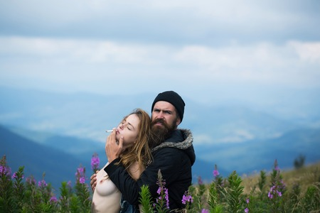 Romantic couple of pretty girl with chest and handsome bearded man in love embrace on cliff on summer day over mountain tops and sky