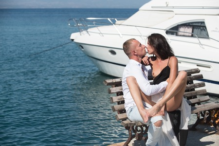 Sexy woman and man kiss on bench. Couple in love with sexy body relax near yacht. Summer holidays and paradise travel vacation. Love relations of naked couple at sea water. Family and valentines day 版權商用圖片