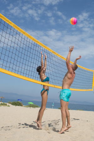 Sport activity and health. sport concept with playong volleyball couple in summer vacation on beach. Stok Fotoğraf