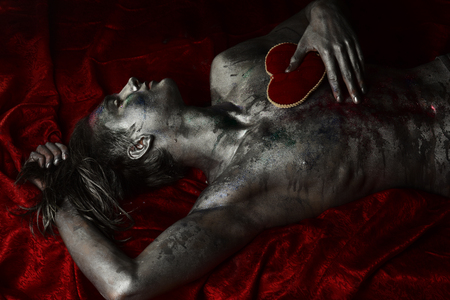 Man with nude torso holds red plush soft heart toy on chest, dark background. Macho on mysterious face with make up, covered with shimmering silver paint and colorful glitters. Valentines day concept. Foto de archivo