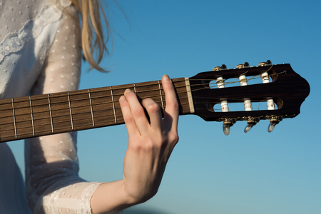 Womans hand playing acoustic guitar instrument, closeup. Stock Photo
