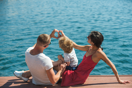 heart shape of hands by happy family on summer vacation. heart of love at sea.