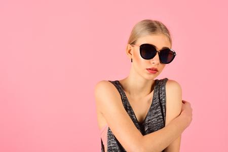 Closeup portrait of blond model with ponytail in melange gray sleeveless blouse wearing big black sunglasses isolated on pink background. Summer eyewear fashion. Stock Photo