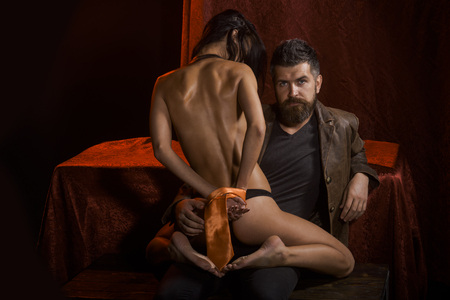 Sexy woman with tied hands, buttocks. Erotic games, sex, orgasm, girl and man. Love, man and woman with tied hand. Couple in love, bdsm, bearded man and naked girl. Dominance and submission, couple. Foto de archivo