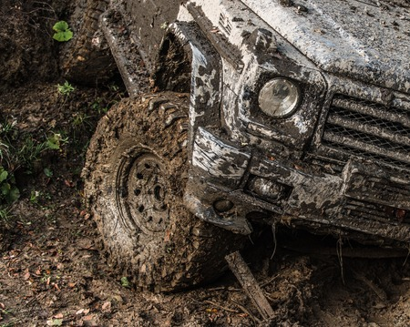 Dirty wheel of car after offroad race. SUV in autumn forest, fallen leaves. Car on country road covered with mud. Impassibility of roads concept. Stock Photo - 103385248