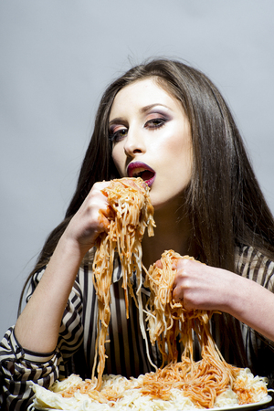 Sexy woman eat spaghetti with hands. Hungry girl have italian food meal. Beauty model with makeup and long brunette hair have dinner. Woman eat pasta dish with tomato ketchup. Food, diet and cuisine. Stockfoto