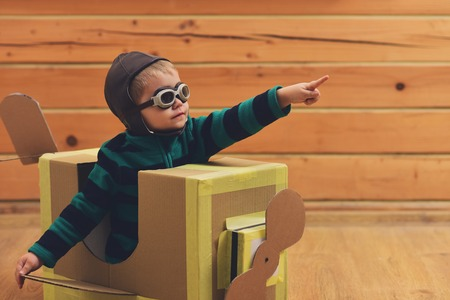 Little boy child play in cardboard plane, childhood. Dream, career, adventure, education. Kid, pilot school, innovation. Pilot travel, airdrome, imagination. Air mail delivery, aircraft construction. Фото со стока