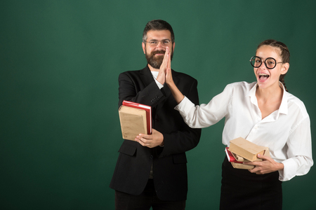 Two students clap hands together with bookd on green blackboard background, copy space