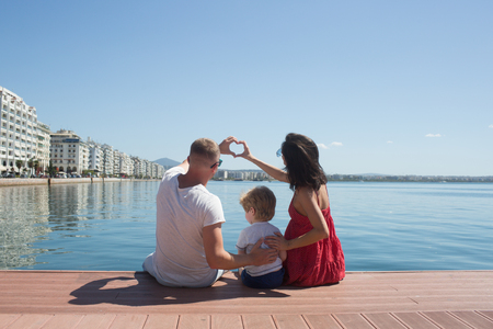 Happy family on the beach. People having fun on summer vacation. Father mother and child against blue sea and sky background. Holiday travel concept Reklamní fotografie