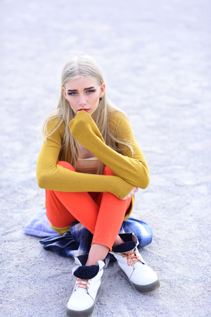 Young hipster girl in bright outfit sitting on street with legs crossed. Blond model with straight hair posing outdoors.