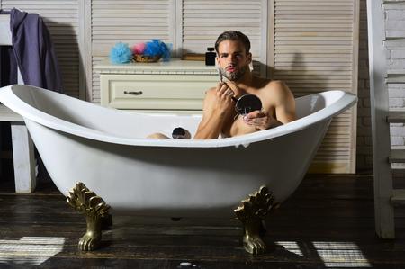 Man shaving with razor blade and shaving cream in bathroom Stockfoto