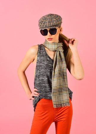 Slim blond model in tartan cap and scarf wearing big black sunglasses isolated on pink background.
