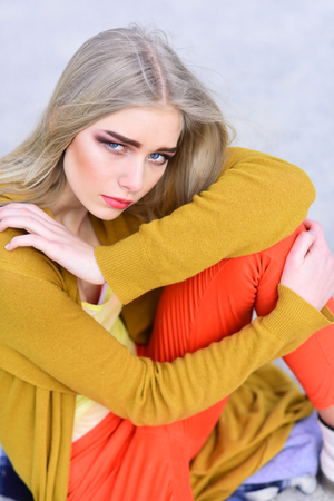 Closeup blond model with thick eyebrows and blushed cheeks sitting on the floor. Girl in bright outfit posing outdoors.