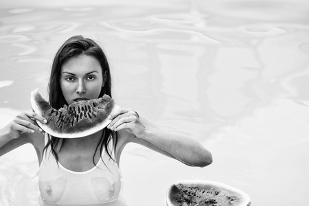 woman with watermelon in pool
