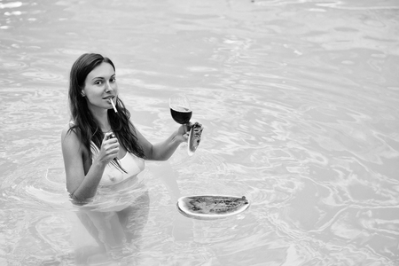 girl smoking with watermelon and wine in pool Stock Photo