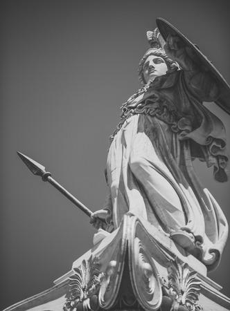 Statua, scultura del guerriero greco in elmo con lancia e scudo. Scultura bianca antico dio greco della guerra con doratura. Statua dell'uomo in armatura con cielo blu su sfondo Archivio Fotografico