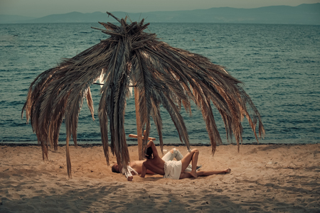 Topless woman and man lie under umbrella made out of dried palm leaves. Couple on vacation at tropical seashore, honeymoon. Love concept. Couple in love full of desire at beach, sea background