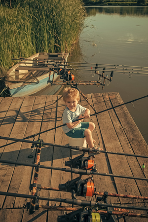 Boy with fishing rod catching fish in the summer Stock Photo