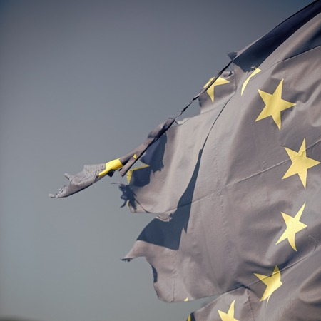 European union twelve star flag torn and with knots in wind on blue sky background, close up. Flag is torn off at side, symbol of problems, decay, disintegration, decomposition, breakdown.
