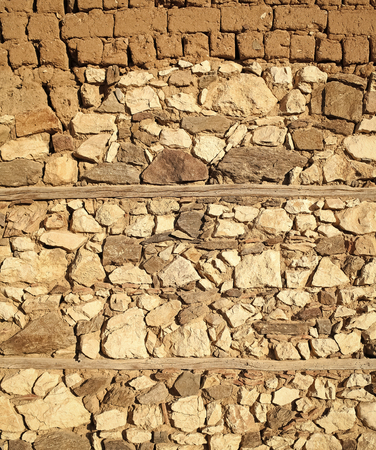 Old beige stone wall background texture, close up. Ancient wall made out of stones and bricks. Textures and background concept. Part of ancient building, architecture.