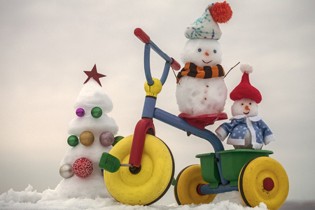 Snowmen riding tricycle on snowy background Stock Photo