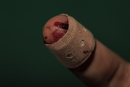 Finger with red blood and plaster on green background