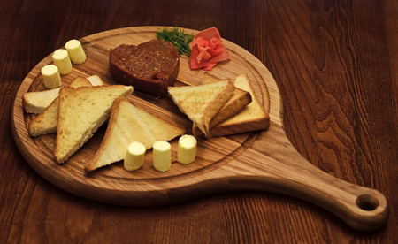 Tatar beefsteak served in shape of heart on round wooden board. Bread, toast and butter around beefsteak on board. Restaurant dish concept. Dish appetizing decorated with dill Zdjęcie Seryjne