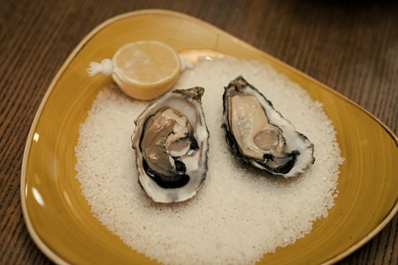 fresh oyster shellfish in luxury restaurant. eating oyster with lemon and crushed ice. healthy delicacy with omega 3 vitamin. Seafood and Mediterranean cuisine. Dieting and health Stock Photo