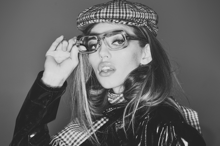 Woman on pensive face with make up wears checkered accessories and glasses for vision. Sexy lady in stylish outfit, close up. Accessories concept. Girl wears kepi, scarf and glasses, grey background