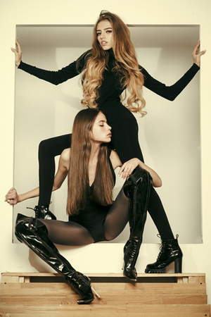 Fashionable ladies with make up and skinny legs posing, white background. Girls with long hair on mysterious faces posing in black clothes. Fashion and beauty concept. Ladies slim wear tight clothes