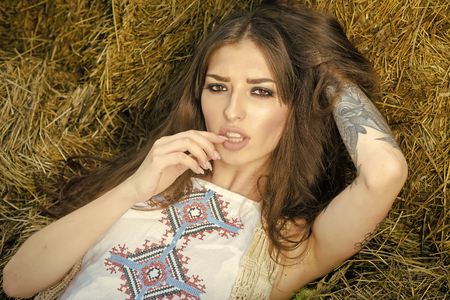 Pretty young country woman on bales of hay