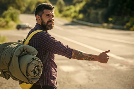 Man with backpack hitchhiking on road
