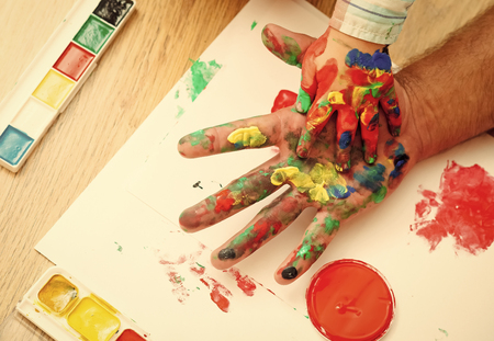 Hands in colorful paints and multicolor palette on white paper