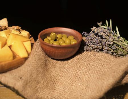 Olives, cheese and lavender on sack cloth Stock Photo