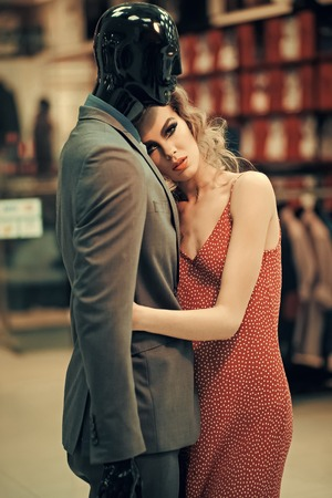 Girl with male mannequin in clothing shop, shopping