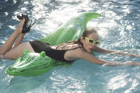 swimming pool with young woman in crocodile skin shoes. swimming pool with girl on inflatable crocodile