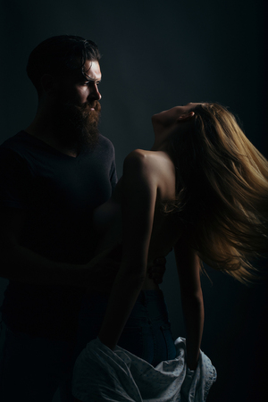 young couple silhouette of handsome bearded man with long beard and pretty sexy woman or girl topless with naked back and red hair in studio on black background