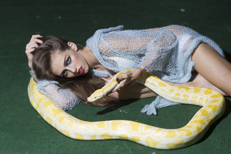 Sexy young woman posing with albino python against green background.
