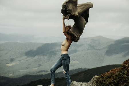 Pretty naked girl slim sexy model with long hair and bare chest in jeans with blanket stands on slope in summer on mountains covered with forest and sky