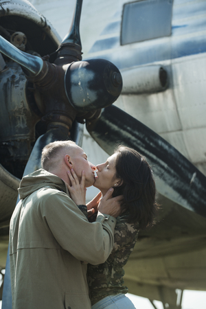 Couple kissing in front of propeller of old plane on sunny day. Couple in love full of desire hugs near airplane on background. Couple on excursion to museum of aviation in open air. Passion concept.