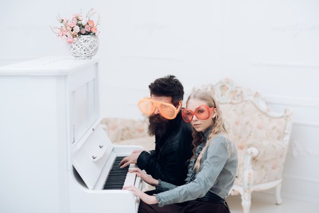 Young couple in enormous glasses sitting in white room and playing piano. Stylish beaded man and his blond girlfriend crazy sitting at grand piano.