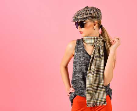 Side view skinny blond model in tartan beige cap and scarf and black sunglasses isolated on pink background. Girl in bright orange pants playing with her ponytail.
