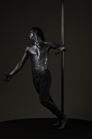 Fashion shot of young sexy mysterious athlete. Macho with naked chest, athlete, sportsman hold metallic pole. Stock Photo