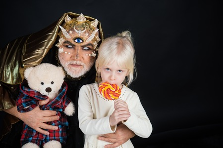 Senior man with white beard dressed like monster telling story to little girl. Fairytale concept. Man with thorns or wart with child sitting on his knees. Demon with golden hood on black background.