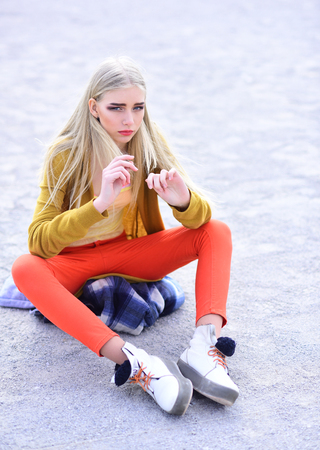Blond model with thick eyebrows and blushed cheeks sitting on sandy road. Girl in bright outfit posing outdoors. Street fashion concept.