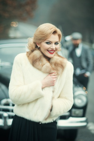 close-up portrait young beautiful stylish couple bride in a white fur coat with groom in retro car on the way to their honeymoon