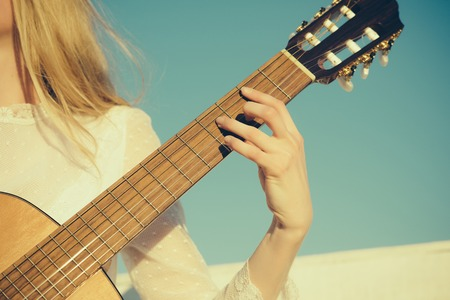 Music and entertainment concept. Guitar with fingers strumming strings. Hand play on string instrument. Classic guitar neck fretboard and headstock on sunny blue sky.