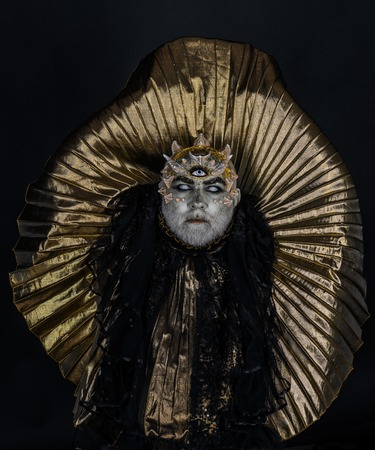 Man with third eye, thorns or warts. Demon with golden collar on black background. Alien, demon, sorcerer makeup. Horror and fantasy concept. Senior man with white beard dressed like monster.