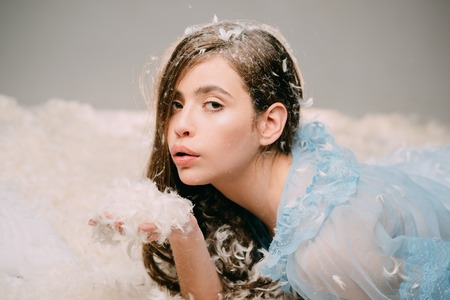 Woman with long hair holds feathers in hand and blow. Lady in transparent blue nightie lay on bed. Feather allergy concept. Girl on calm face lay on bed covered with feathers and fluff.