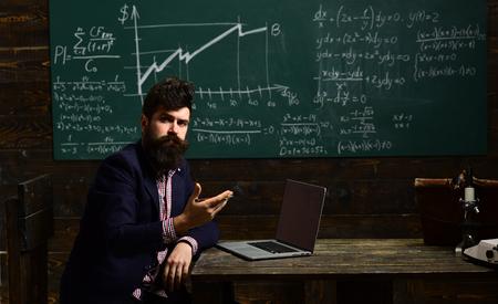 Bearded man is tutor or teacher. Portrait of female teacher using modern technology laptop in her class. In teachers classroom. E-learning. Private tutors often have vast teaching experience. 写真素材